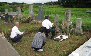 お墓参りをする家族