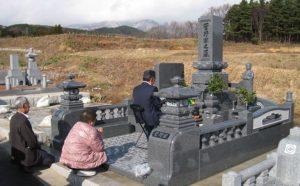 新しくしたお墓参りをする家族